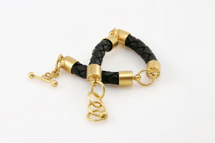 Fruit Bijoux, Tamer, gold bracelet with braided black leather. To download high or low resolution product images view Mondrianista.com (editorial use only).