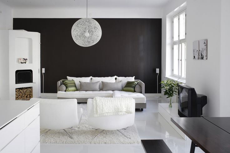 I'm usually not too fan of black & white interiors but this one works really well with the deep black wall and the green details