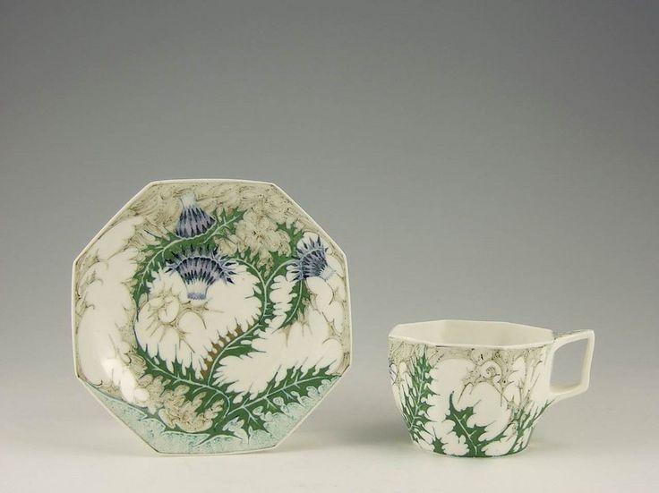 Een eierschaalporseleinen servies met een achtkantige kop, schotel en bord, beschilderd met distels. Het kopje (model225) is 6 cm hoog, diameter van het schoteltje (model 14) is 14cm en de diameter van het bord (model 15) is 21