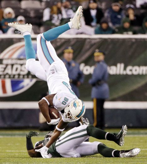 Miami Dolphins tight end Dion Sims (80) is tripped up by New York Jets inside linebacker David Harris (52) during the second quarter of an NFL football game, Monday, Dec. 1, 2014, in East Rutherford, N.J. (AP Photo/Julio Cortez)