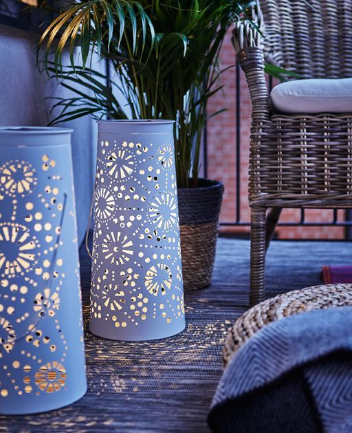 Two decorative, metal, solar-powered lanterns light the balcony during the evening. IKEA