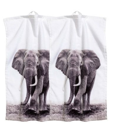 White/elephant. Guest towels in velour with a printed photographic design at front and terry at back. Hanger loop on one short side.