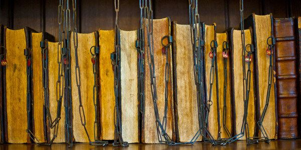 Most of the chained books were left to the Royal Grammar School in Guildford, England, by the Bishop of Norwich in his will. While they were endangered by a fire in the 1960s, the books still survive in their locks, although kept in the Headmaster's Study. Now the books with their age and rarity are just as valuable, if not more so, as when they were first cuffed into place, and it's likely the confining chains had something to do with their preservation.