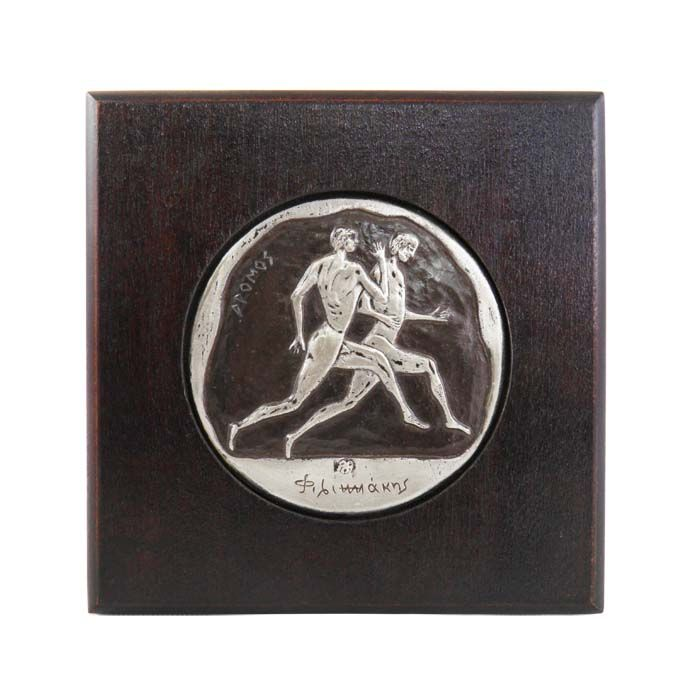 The stadion race was one of the several running events in Ancient Olympia and the first and only event in the ancient Olympic Games, until 728 B.C.. The depiction of the sport is inspired by the representation of a running race on an ancient panathenaic amphora. Ancient Olympia, Greece Dimensions: 14cm x 14cm x 2cm Copper patinated plaque, plated in silver solution 999°, mounted on wodden frame.