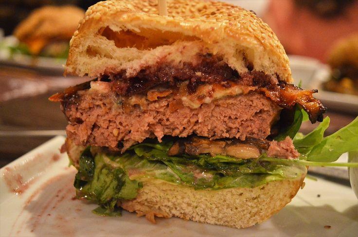 L'Amour (R$36,00) é um burger de 180g de carne bovina, quejo roquefort, cogumelos salteados na manteiga e toque de molho shoyu, tiras de bacon crocantes, mix de folhas verdades, geléia de framboesa com vinho tinto e molho da casa.