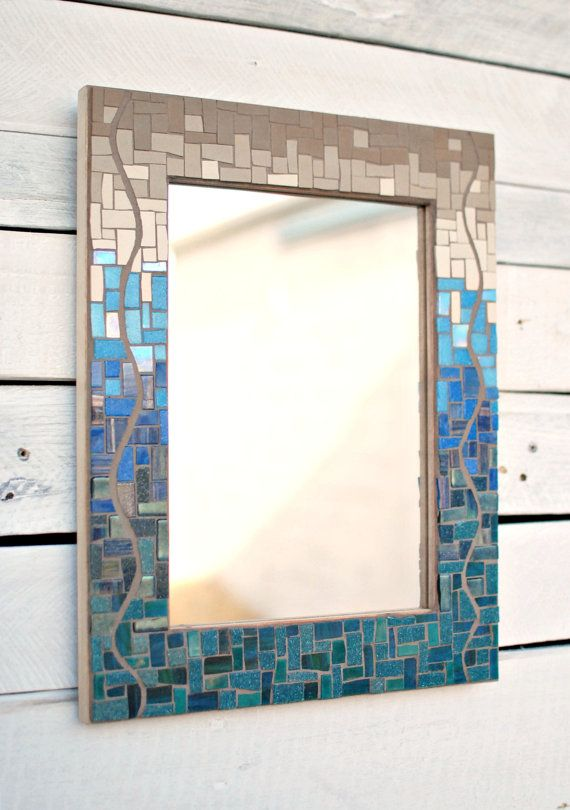 This mosaic mirror features a shift in color and texture, from shiny glass in teal and royal blue at the bottom, to flat unglazed porcelain in