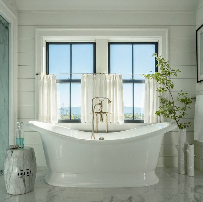 Farmhouse bathroom with black pane windows, cafe curtains and free standing bath. Wall paneling is tongue and groove. #Farmhousebathroom #blackpanewindows #cafecurtains #freestandingbath #paneling #tongueandgroove Roundtree Construction. TruexCullins Architecture + Interior Design