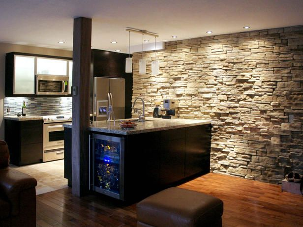 modern kitchen remodel features black cabinetry, sleek surfaces, hardwood and tiled floors, recessed lighting and a custom stone wall that gives the space a wine cellar feel.