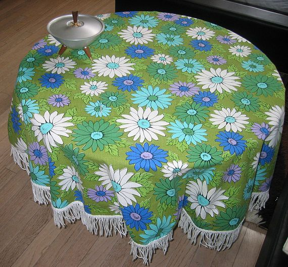 Vintage Daisy Round Fringed Tablecloth (or Fabric reuse)  Great 60s daisy motif in blues and greens. Fabric: Heavy cotton duck  Size: Round, 47 inches plus white fringe  Condition: One small rip that could be repaired by stitching (see photo). I have priced the tablecloth accordingly since you will have to sew it up. Slight stain on fringe, did not try and bleach out. Questions? Please ask. Thanks for looking.  (Note: Sale is for one tablecloth, not accessories.)