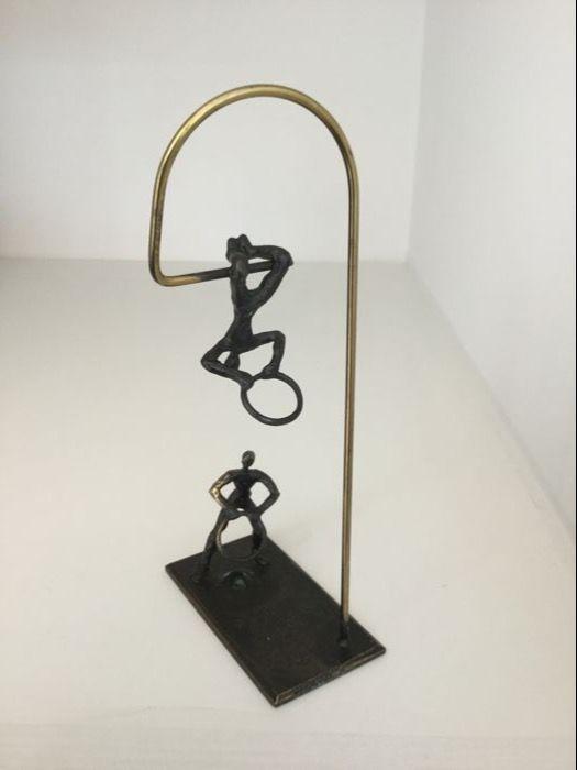 """Corry Ammerlaan van Niekerk - bronzen sculptuur """" Samenwerking """"  Mooi bronzen sculptuur van de beroemde Nederlandse kunstenares Corry Ammerlaan van Niekerk .Het sculptuur laat zien dat twee acrobaten elkaar op het juiste tijdstip ringen toewerpen ; echte samenwerking !Is gesigneerd : CANMateriaal : brons.Hoogte : 195 cm.Het sculptuur mist helaas de sokkel waar het oorspronkelijk op heeft gezeten.Verder verkeert het sculptuur in goede staat en wordt het zorgvuldig verpakt en aangetekend…"""