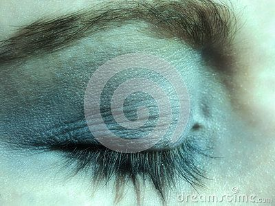 A close-up view of a teenage girls eye with blue eye shadow.