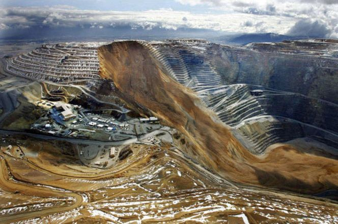 Utah's Bingham Canyon Mine, one of the largest active copper mines in the world, had a massive landslide last night, which makes for quite an extraordinary coppery blur against the orderly terraced geometry of the hole itself.