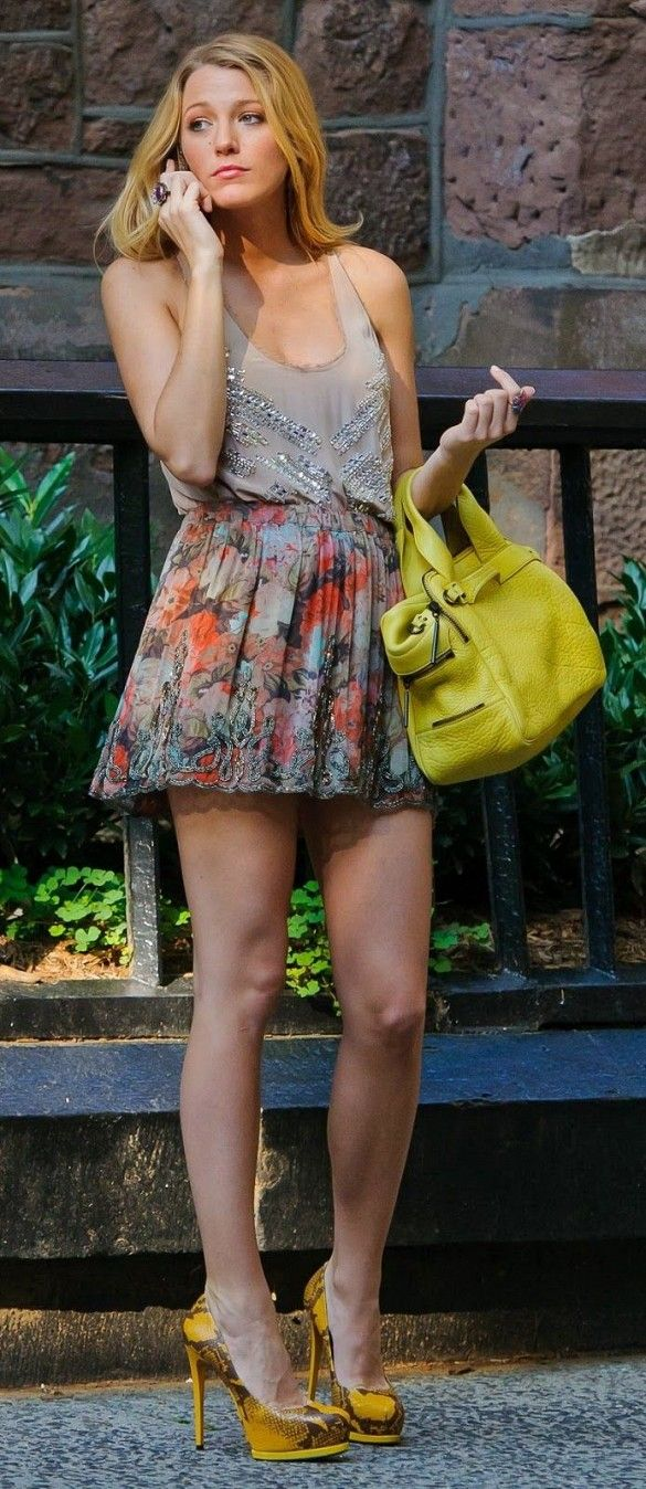 Blake Lively wears an embellished tank, floral skirt, heels, and yellow bag on the set of Gossip Girl