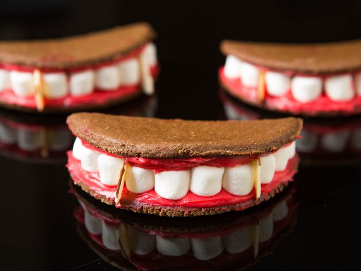 These fun and easy vampire mouth cookie sandwiches take their inspiration from s'mores, with a chocolate-graham-cracker mouth, red-dyed frosting gums, mini-marshmallow teeth, and almond-sliver fangs. #halloween #familyfun #kidfriendly #recipe #spooky
