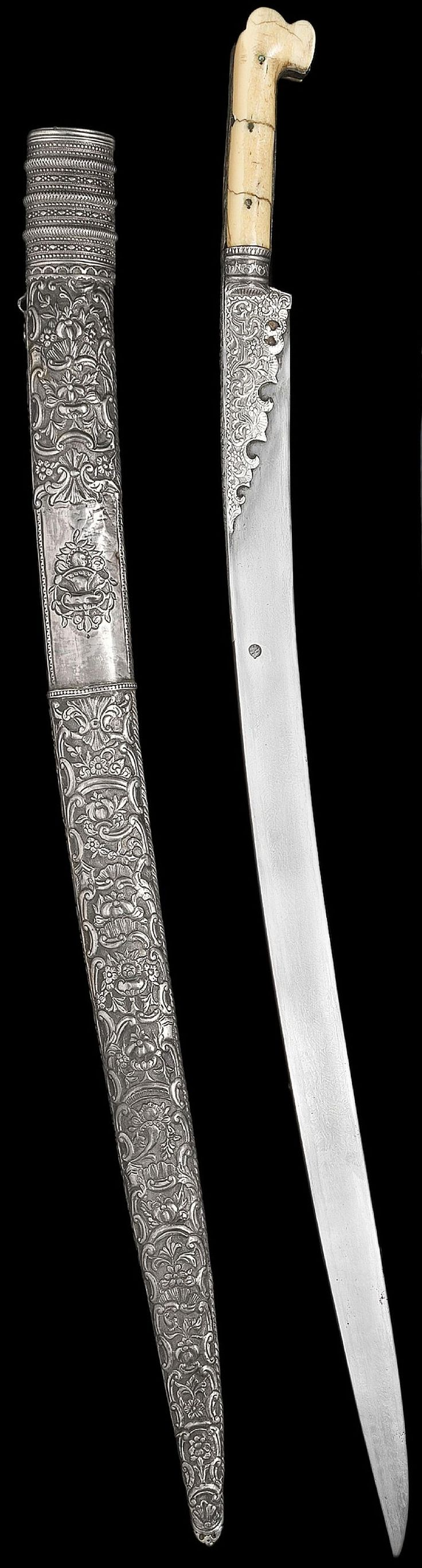 Ottoman yatagan, 19th century, with slightly curved tapering single edged watered steel blade with makers mark, the forte and centre of the ivory hilt mounted with embossed silver, decorated with continuous rococo style floral interlace, its wood scabbard entirely covered in silver elaborately embossed with rococo style foliage and urns containing floral sprays, 77.7 cm. long.