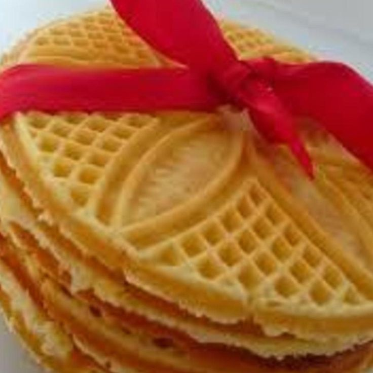 """Pizzelles are light wafer cookies made from a simple batter flavored with a hint of lemon or in this case, maple. The batter is cooked on a special pizzelle iron (also known as a cialde iron) which embosses the cookies with decorative patterns such as flowers and stars. In central Italy, where the pizzelle originated, families would choose their own distinctive patterns and pass them down from generation to generation. These are a tradition for Italian families in R.I. & Mass""."