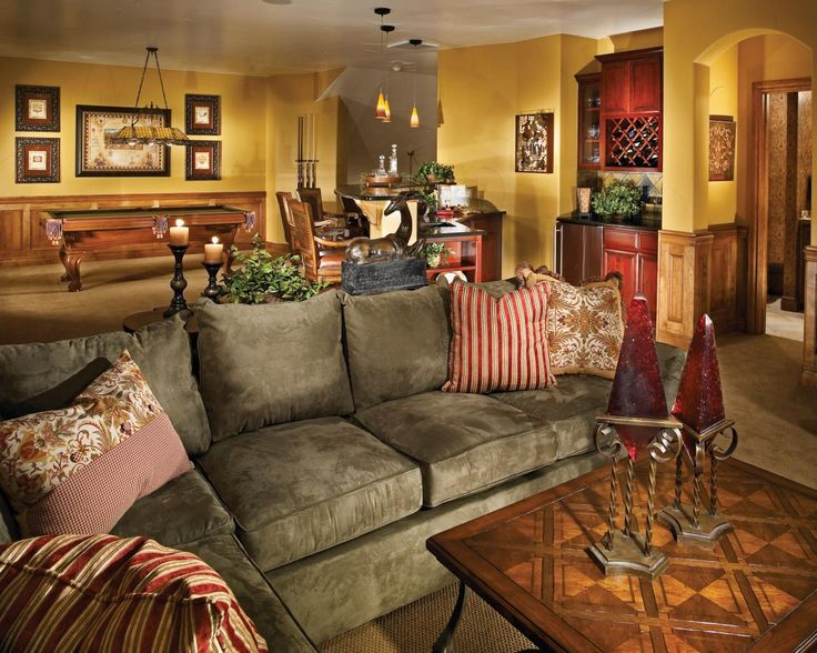 Eclectic furniture and art fill this bright yellow basement lounge area. A gray sectional with funky patterned pillows creates a unique and comfy spot to relax.