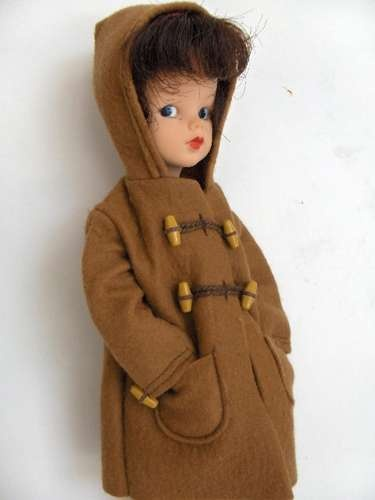 A first issue brunette Sindy doll wearing the toggled brown Duffle Coat fashion, United Kingdom, 1963-64, by Pedigree Toys.