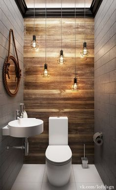 this beautiful small bathroom has low hanging industrial lighting that works perfectly with the wood paneling