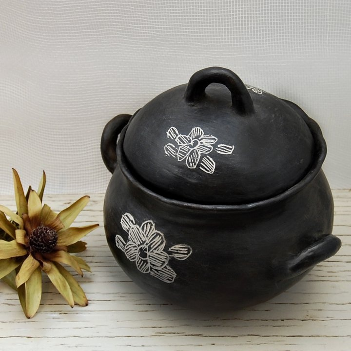 Olla de cerámica negra de Quinchamalí con dibujos de flor.