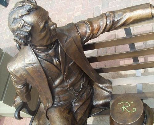 These thoughts struck me as I walked past Charlottetown's newest public art display, a copper statue of Sir John A. MacDonald sitting on a bench at the corner of Queen and Richmond Streets. Since its installation earlier this year, I have witnessed countless pedestrians interacting with this brass replica