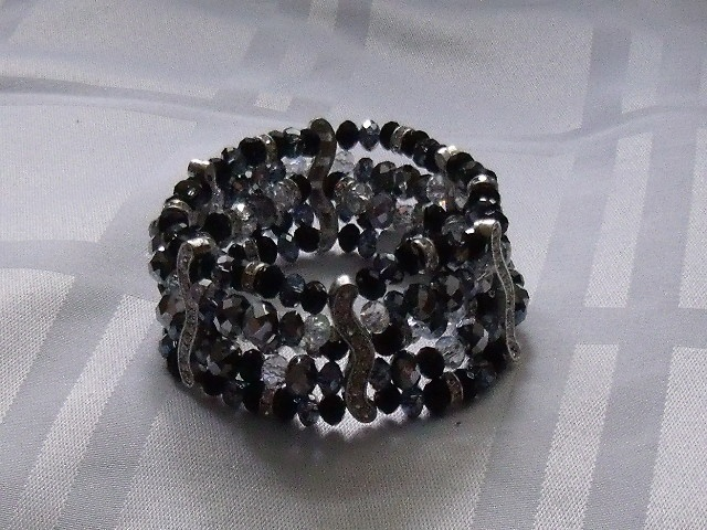 This stunning black, silver and white chinese crystal elastic braclet featured 5 layers. It is a past piece and no longer available. Other similar designs can be made