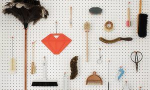 A white pegboard in the utility room stores cleaning stuff neatly
