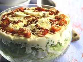 Salát s vejci, ledovým salátem, rajčaty a strouhaným sýrem.