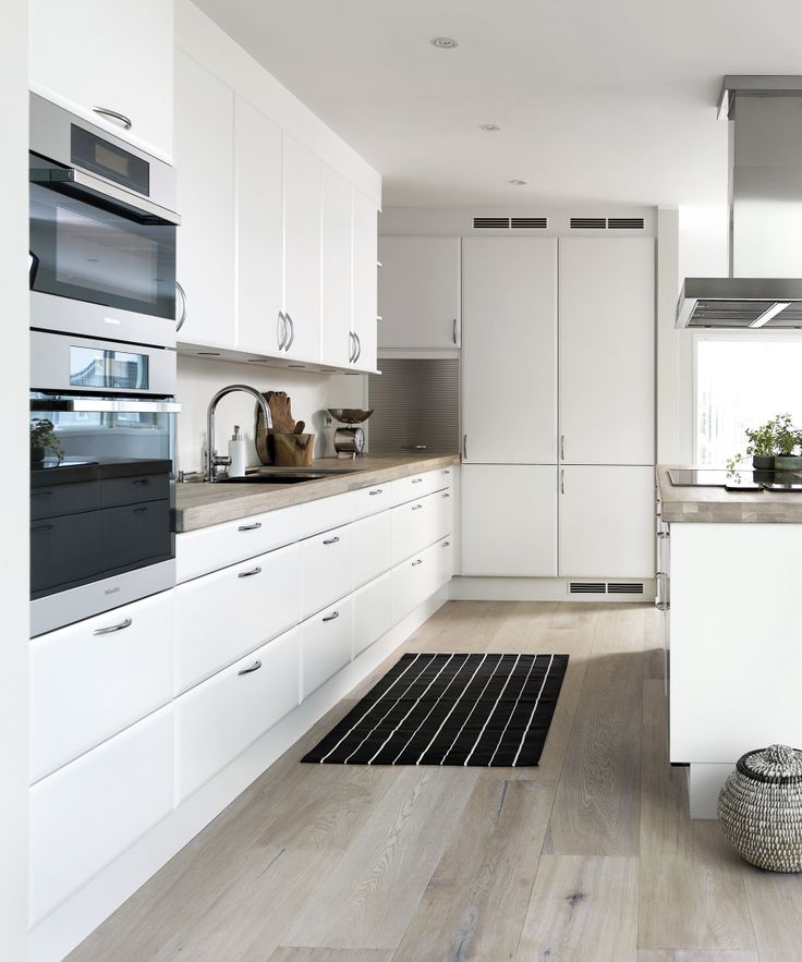Køkkenet er indrettet enkelt og klassisk med hvide overflader, der får et blidt modspil af bordplader i olieret eg. Se boligen på www.jke-design.dk.