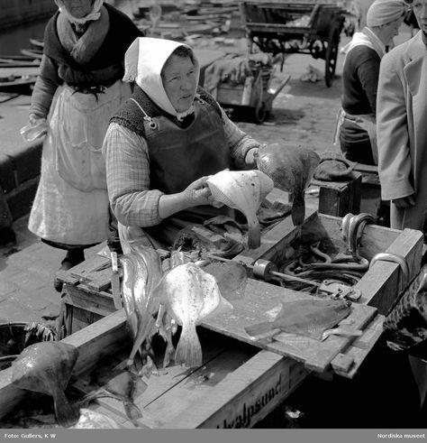 Torghandel, Stockholm, 1946. Äldre kvinna med huckle på huvudet säljer fisk. Foto: K W Gullers