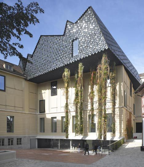 Architects Herzog & de Meuron have positioned a scaly crown over the top of this Basel museum