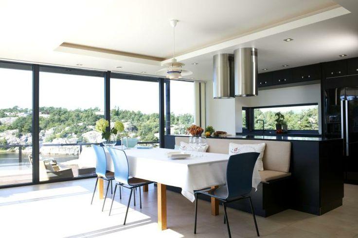 PRAKTISK: Kjøkkenet er avdelt med en stor kjøkkenøy som også virker som ryggstøtte til spisegruppen.Benkeplatene er i polert stein. Over induksjonstoppen er det montert lys og vifte i to rør i børstet stål fra Gorenje.