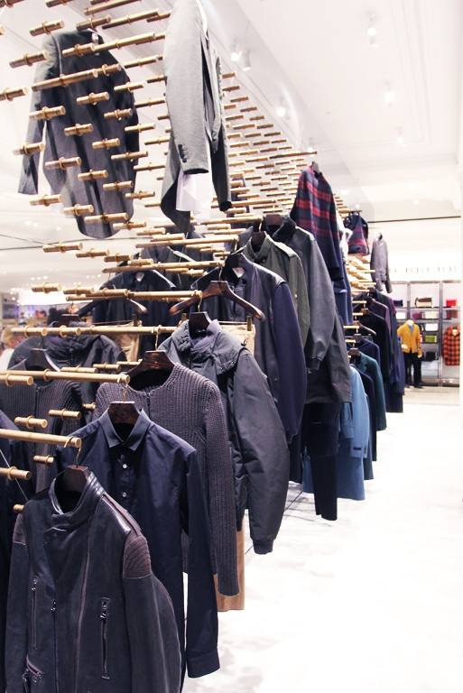 Selfridges London Men's Designer Space has managed to manipulate the positioning of an array of mens blazers.  Wooden pegs are erected from a mirror - the blazers attached upon wooden hangers. The reflection of the blazers give the illusion of 2 suits instead of one. The power of plenty shows of importance as well as the use of mirror to widen the space.