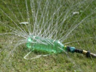 "This spinkler is a simple recycle project that can be a lawn spinkler or just a devise that the kids can use to get wet!  Materials:  1 Empty 24oz soda bottle  1 Plastic coat hanger with or without hook  2 Large rubber bands  1 Hose end replacement kit 5/8""($1.67 at Lowes)  1 Rubber washer for swivel hose end  Mighty Putty  Tools:  Drill & bits"