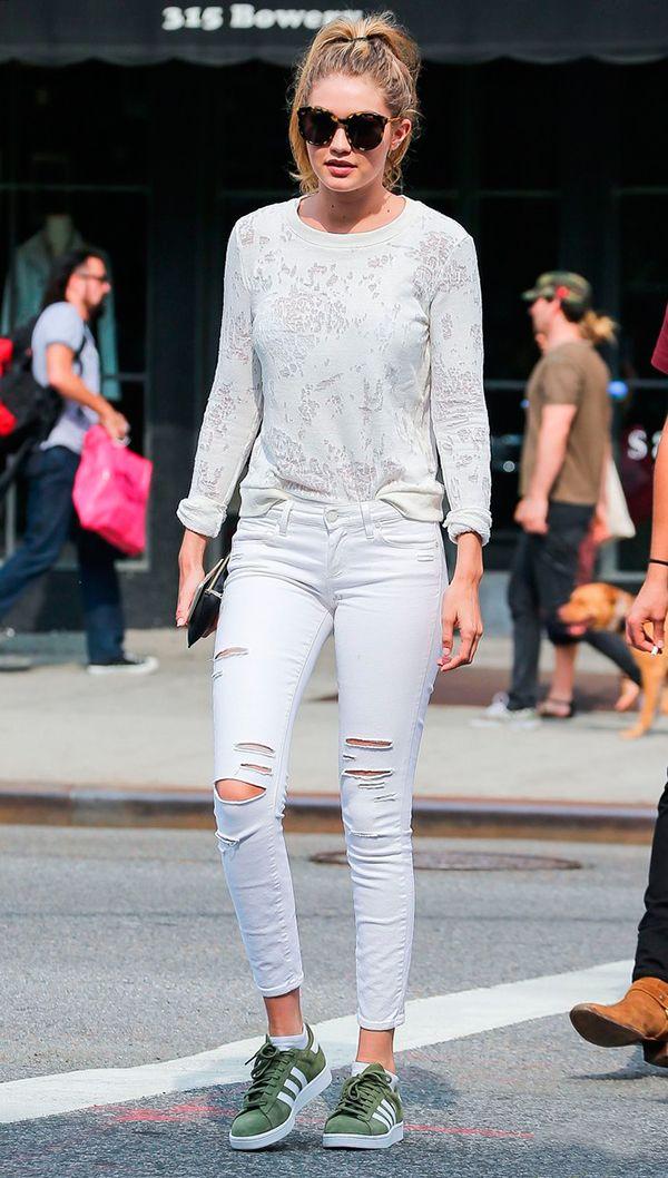 Gigi Hadid usa look clarinho com blusa off white, calça jeans destroyed branca e tênis adidas gazelle verde