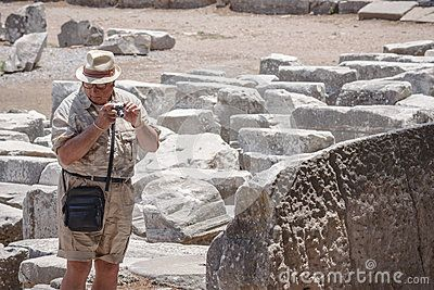 A tourist man is shooting photos in Ephesus: antique greek, later roman, city in the actual Turkey; near Izmir. The man is holding a compact camera in his hands and searching subjects to shoot