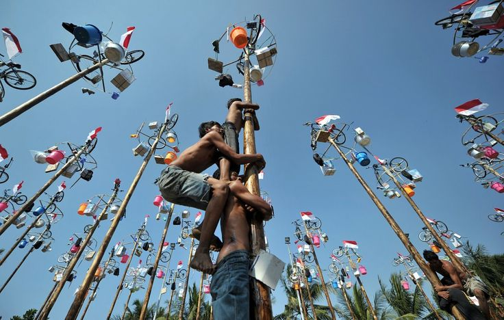 People attempt to climb greased and slippery poles, to which prizes and flags are attached, to celebrate Indonesia's Independence Day in Jakarta. (AFP)