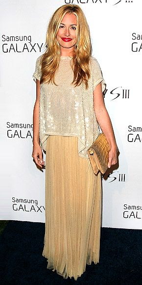 CAT DEELEY attending a Beverly Hills Samsung bash ~ The TV host mixes & matches pieces for a bling-meets-boho effect, topping a pleated beige maxi w/ a paillette-embellished tunic, then finishing the ensemble w/ an oversize gold clutch.