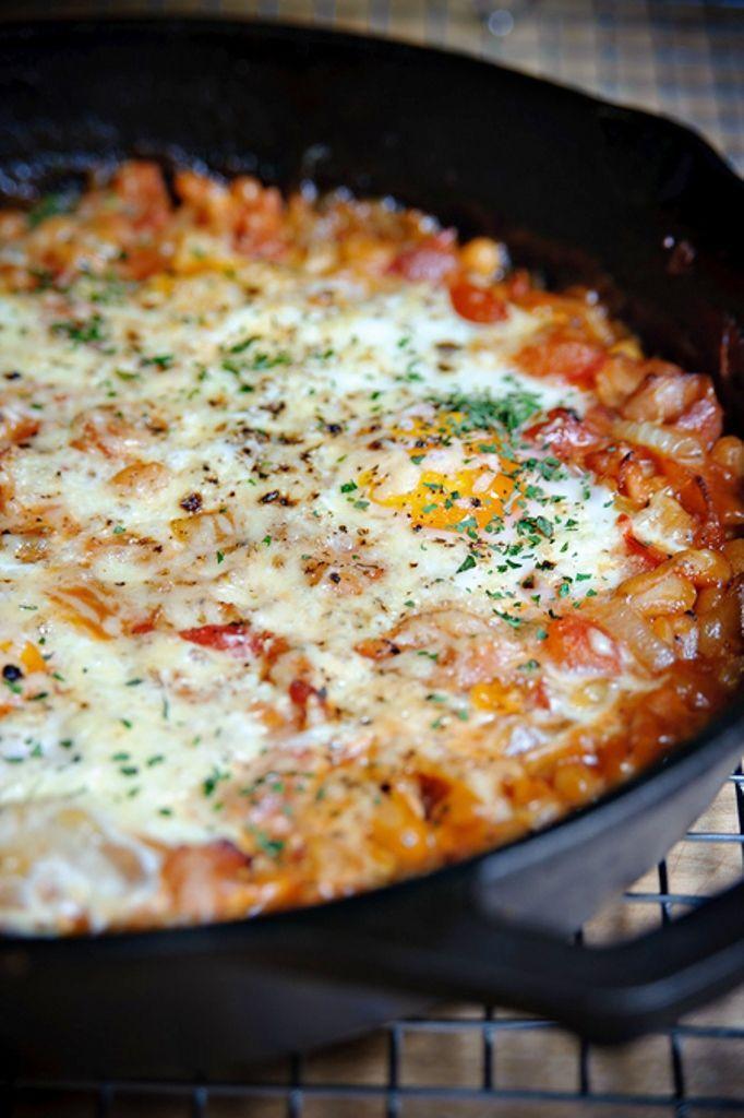 Bereiden:Verwarm je oven voor op 175C° In een ovenvaste koekenpan bak je het spek uit. Voeg een klein klontje boter toe en fruit de uien in ca. 4 minuten aan. Roer de stukjes tomaat erdoor, breng het op smaak met een flinke snuf zout en peper en roerbak het geheel zo'n 2 minuten. Voeg nu de witte bonen in tomatensaus toe en roer alles goed door. Breek de eieren erop uit. Bestrooi ze met wat zout en peper en verdeel de geraspte kaas erover.