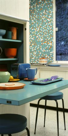 A view of the colourful kitchen at Chert, space saving versatile designs were used, pictured here is a flip down breakfast bar - love the mosaic wall behind.