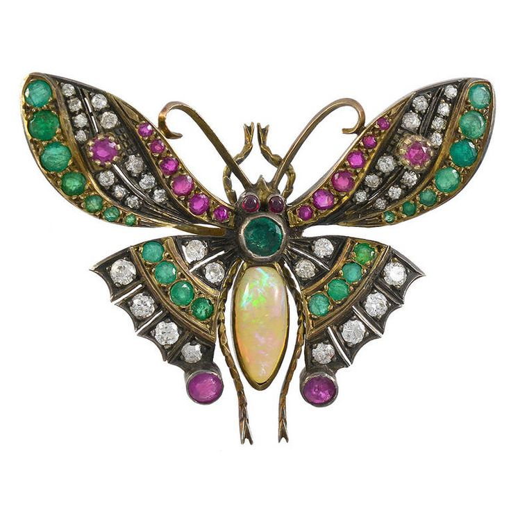 Antique Jeweled Butterfly Pin. 18k gold and silver emerald, diamond and ruby encrusted pin with an opal center. England, circa 1890