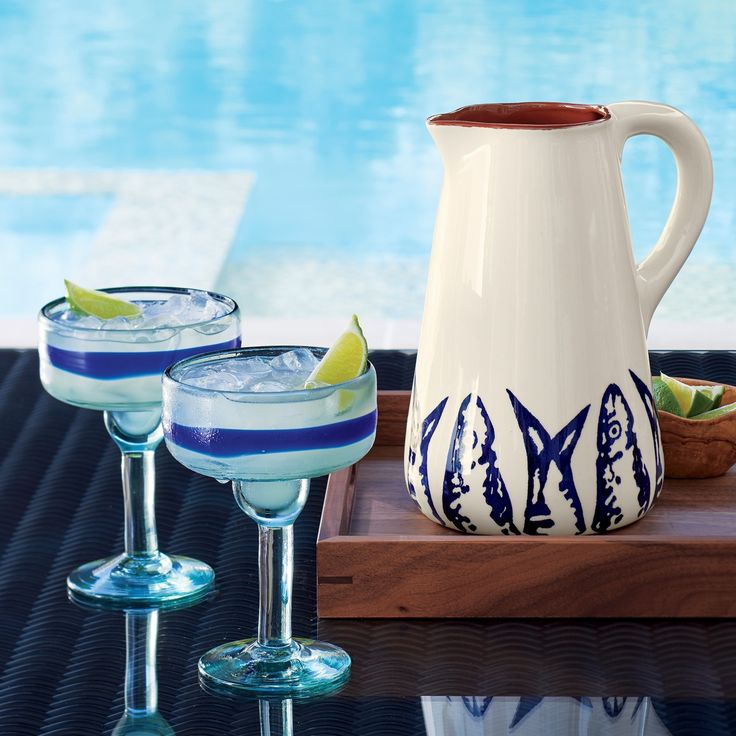 A ribbon of deep cobalt rings these rustic margarita glasses, each a unique creation blown of recycled glass by a team of five artisans. The tall-sided sombrero design is ideal for straight-up or frozen margaritas and other tropical drinks.