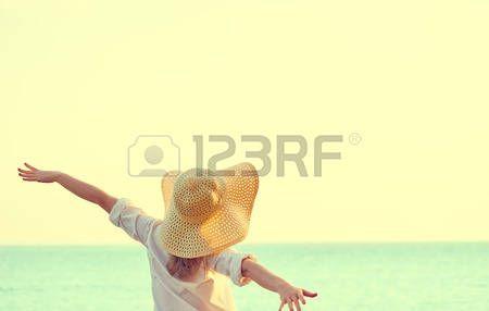 meditacion: Mujer feliz de la belleza en el sombrero está de vuelta abrió las manos, se relaja y disfruta de la puesta de sol sobre el mar en la playa