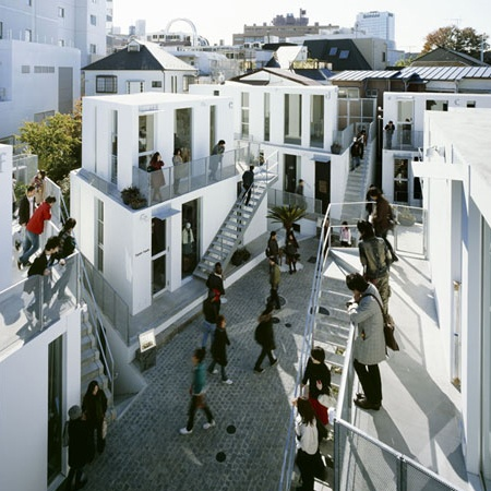 Outdoor shopping mall, Sarugaku, in the Daikanyama district, which accomodates six buildings and ten retailers on less than six thousand square feet; architect Akihisa Hirata does so by means of compression, allowing shops to sit atop one another and relying on shoppers and storefronts to fill an otherwise unadorned public space. Follow us for more daily updates at www.pinterest.com/pilkingtonglass   Tags: #Architecture #Tokyo