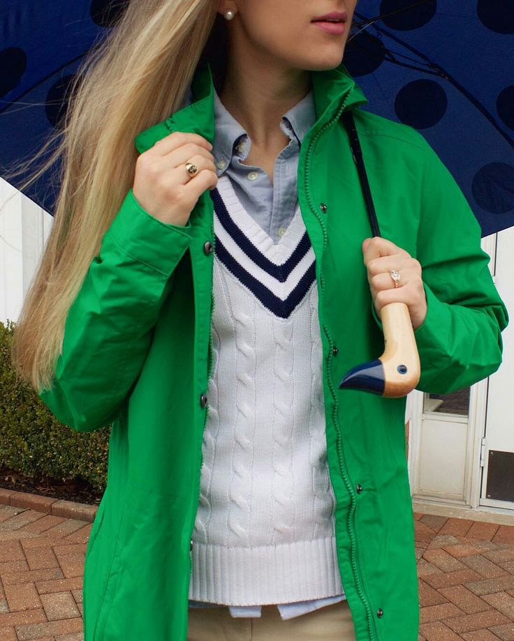 New England Classic Style | Spring green raincoat,  white v-neck cable knit tennis jumper with navy blue ribbon stripes, blue Oxford shirt, navy blue umbrella with black polka dots and wooden duck handle