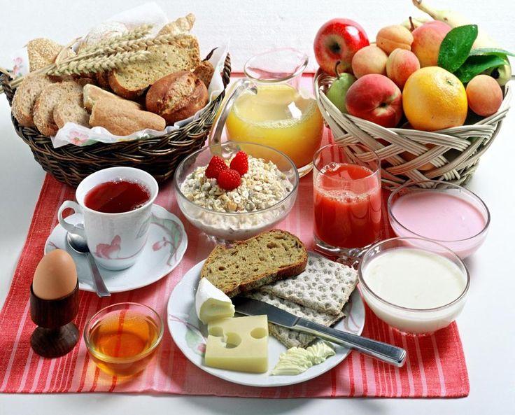 Continental breakfast including: fruit, juice, bread, tea, hardboiled egg, cheese, yogurt and cereal