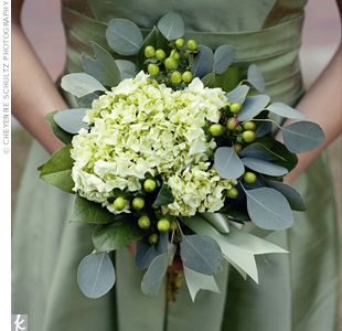 soft green bundles of hydrangeas and berries with the stems wrapped in green ribbon.