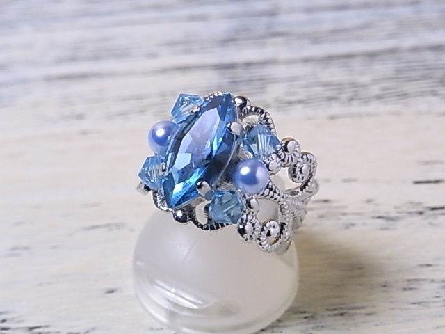 エレガントでインパクトのあるデザインの指輪です。   透かし模様のリング台に、スワロフスキービーズでシンプルに装飾しています。  こちらの色は、爽やかなアクアマリンカラーです。特にスワロフスキーのアクアマリンは、透明度が抜群なうえ、発色もとても綺麗です。   貴方の指先を個性的なデザインで飾ってくれる、お出かけが楽しくなるリングです。  リングサイズは、11号から15号まで調整できる、フリーサイズ使用です。    色:ライトブルー(アクアマリン)   素材:スワロフスキーガラス。スワロフスキーパール。リング台は、銅にロジウムメッキ。  サイズ(およそ):モチーフ部:縦約15mm。横約14mm。リングサイズ:11号から15号のフリーサイズ。