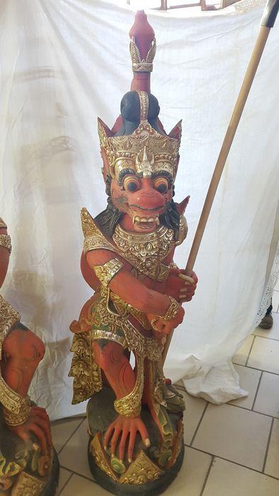 Paar polychrome houten beelden geschilder en goud - Bali - Indonesië  Paar mooie oosterse houten beelden geschilderd in diverse kleuren en goud. Ze zijn in de vorm van fantastische wezens met lans op voetstukEen van de beelden mist het helmteken een deel van zijn kleding en heeft een breuk in het hout door het lichaam. De ander mist het eind van een teen aan de linkerzijde.Beiden hebben enkel sporen van licht gebruik (enkele lichte afbladdering van de kleur).Gezet op voetstukken van zwart…