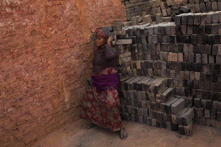 In this Wednesday,  2015 photo, a Nepalese laborer carries a load of bricks at a brick factory in Bhaktapur, Nepal - by Bernat Amangue, Indian